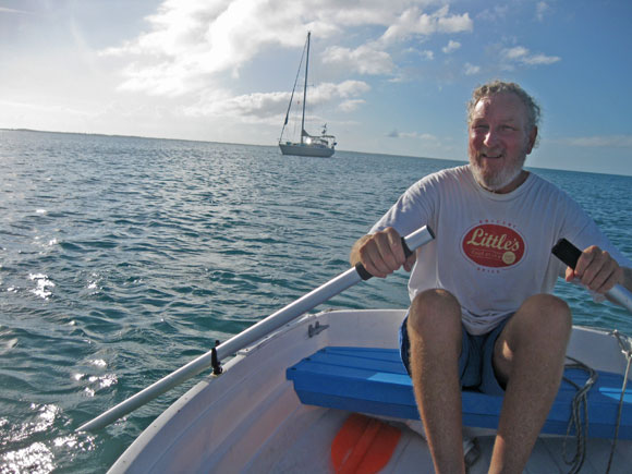 Greg rows Fever at Powell Cay, while Blue Wing holds our spot in the anchorage.