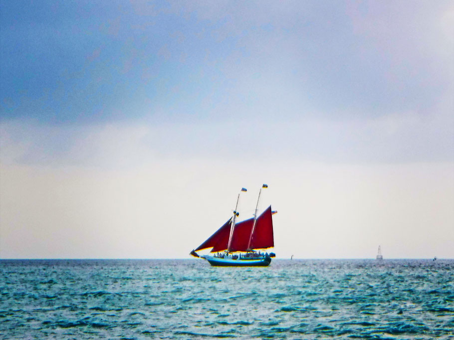 Red-sailed sailboat.