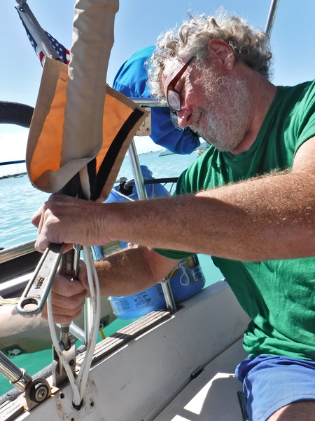 Loosening the backstay turnbuckle to relax rearward tension on the mast.