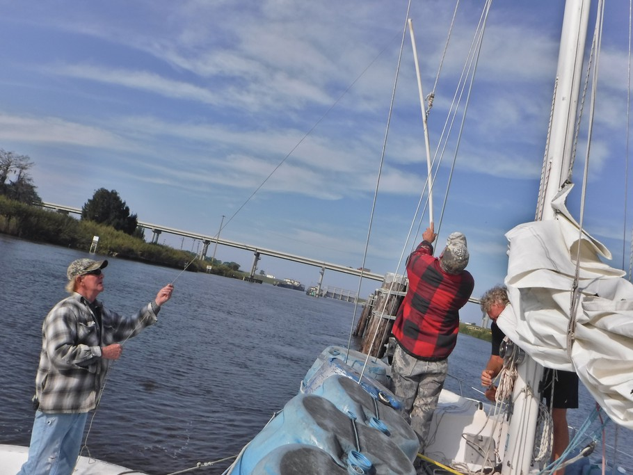 The guys hoist a measuring stick to the top of the mast. If the stick clears the bottom of the bridge the mast will also. A line hanging from the stick trails in the water, measuring the height of the tipped mast.