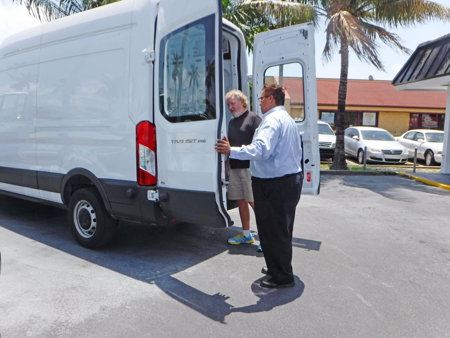 Greg and the salesman look at a Ford Transit Van.