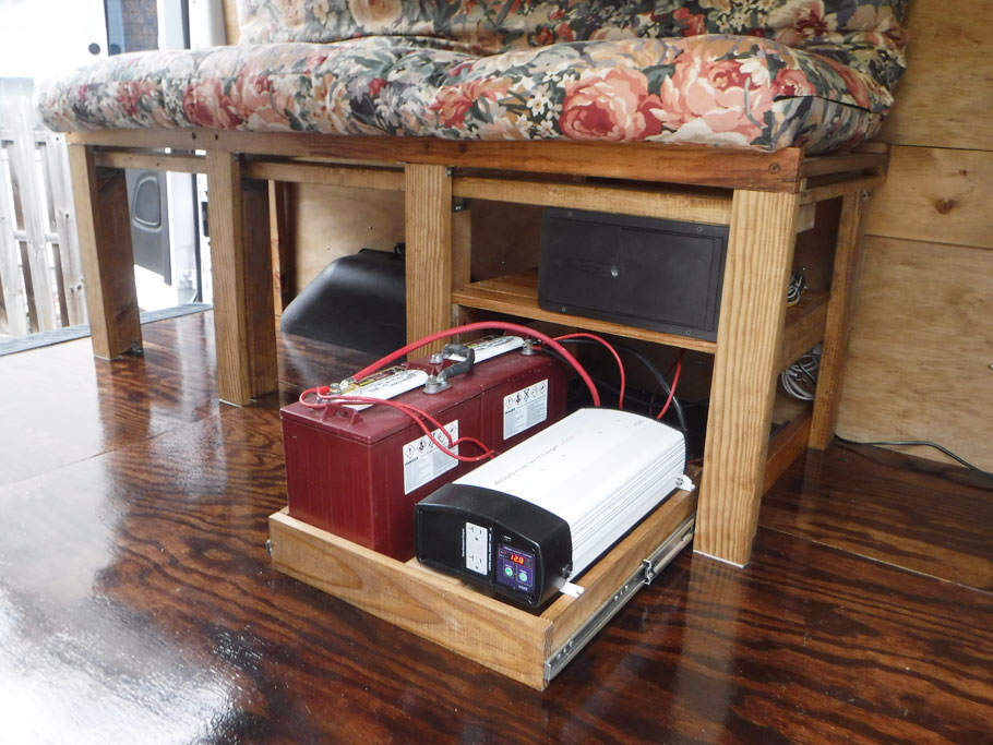Bed frame and power station are set up. Drawer opens so that water can be added to the two red 6 volt house batteries. The black and white 2000 watt inverter sits beside the batteries. The black panel above it is the fuse and breaker box. The rats nest of wiring now runs into the back of this RV fuse box.