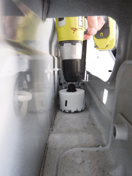 We wanted a vent to the outside so the exhaust fan could draw air in. There is a convenient hole in the undercarriage behind the driver's seat. I just needed to drill out a hole in the floor between the inner and outer walls.